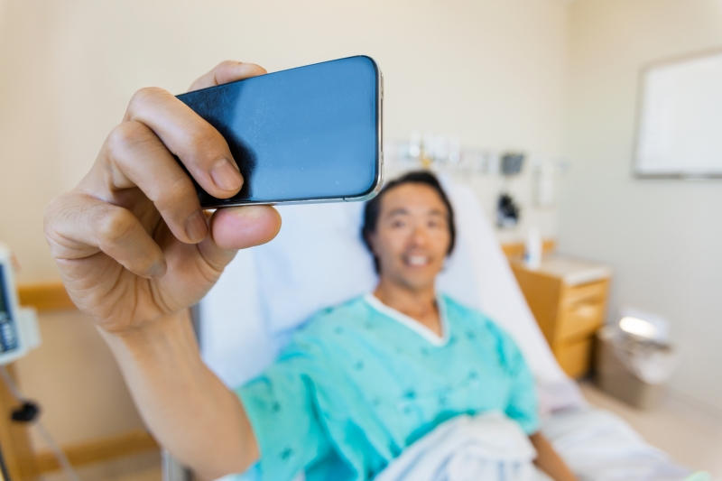 7703273-male-patient-taking-self-portrait-through-mobile-phone-in-hospit